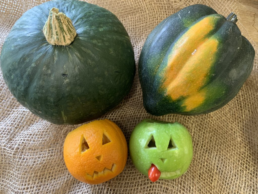Scary! Orange and apple jack-o-lanterns made these poor kabocha squash so scared that one of them toppled over with fright.